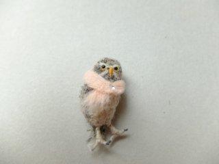 ベビーピンクのマフラーを巻いたアナホリフクロウのブローチ